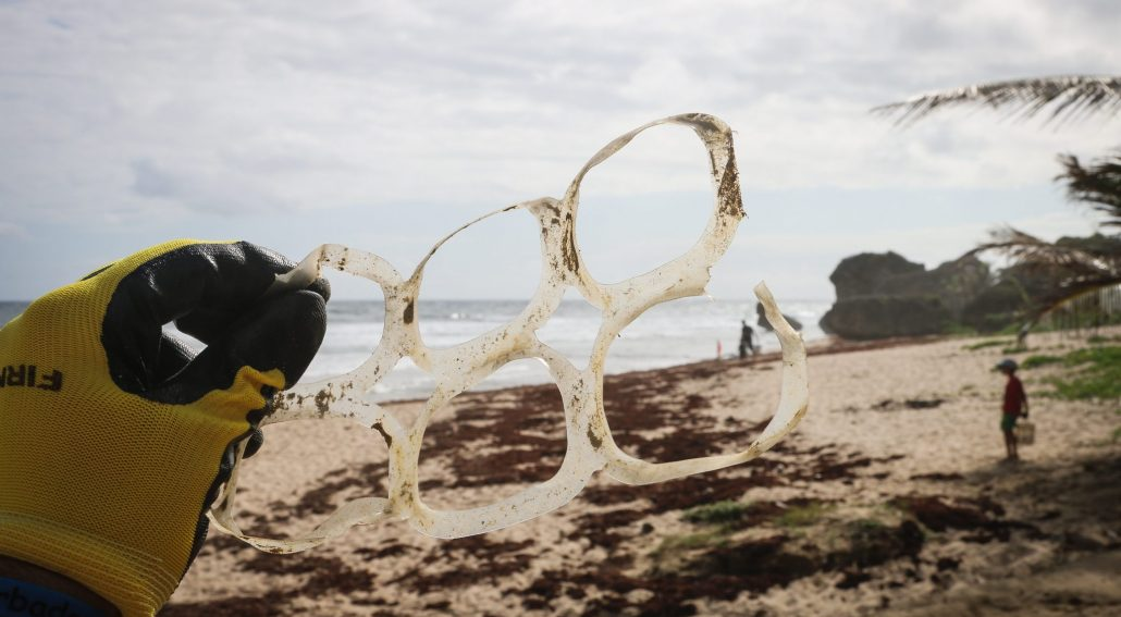 plastic free featured image - man holding plastic 6 ring on beach