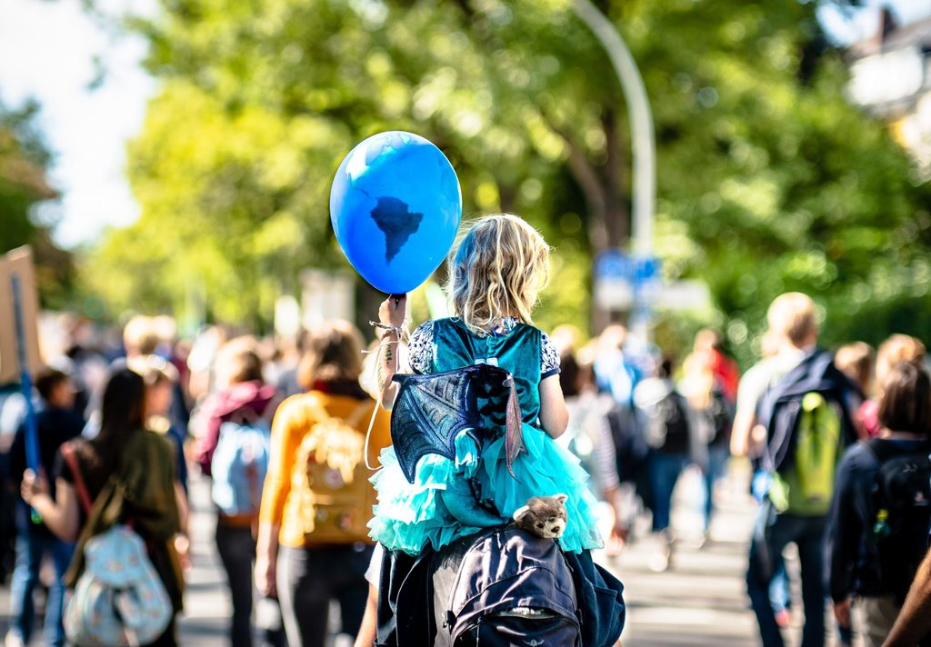 positive climate action girl on the shoulders of a parent with a balloon of the globe