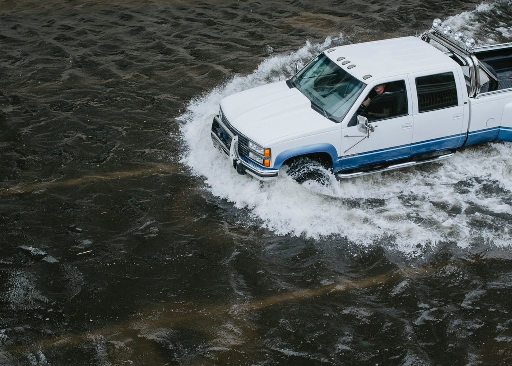 positive climate action car driving through flood