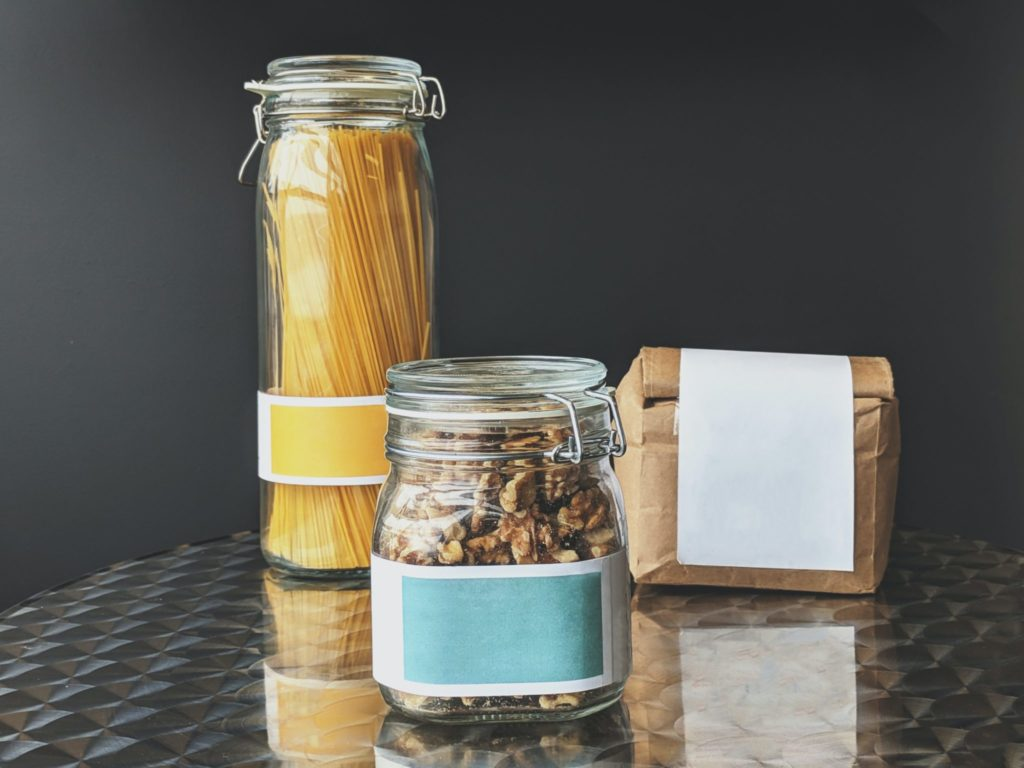 Zero waste packaged items. A jar of pasta. A jar of nuts. A paper bag of flour. Highlighting the move to low waste as a great way of reducing waste, key to this united nations sustainable development goal