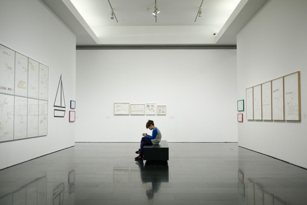 A young person sat in a wide open space at a museum. They are engaged with something in their hands while they sit. They are surrounded by three walls, all with pieces of art work.